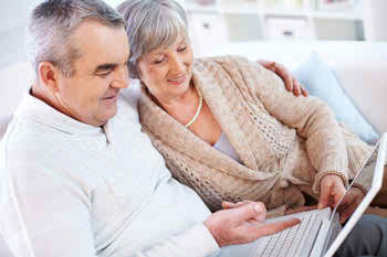 Senior Couple on Laptop looking into Medicare Advantage Dissenrollment