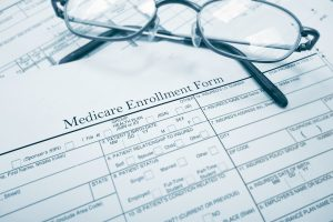 A medicare enrollment paper form and glasses in Annual election period